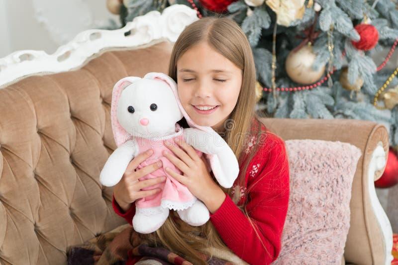 El pequeño juguete más lindo nunca Pequeño juguete del conejo del abrazo de la muchacha El mejor juguete de la Navidad Niña con e fotos de archivo