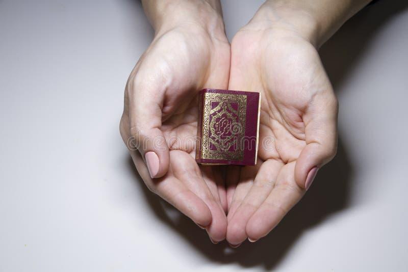 El pequeño libro del Qur 'en las manos de la mujer imagenes de archivo