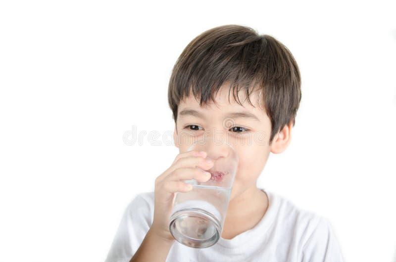 El pequeño muchacho asiático bebe el agua de un vidrio en el fondo blanco foto de archivo