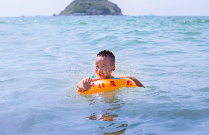 El pequeño muchacho chino nada en la bahía con un anillo de goma en un fondo la isla fotografía de archivo libre de regalías