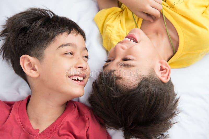 El pequeño muchacho del hermano pone en la almohada en el piso junto imagen de archivo
