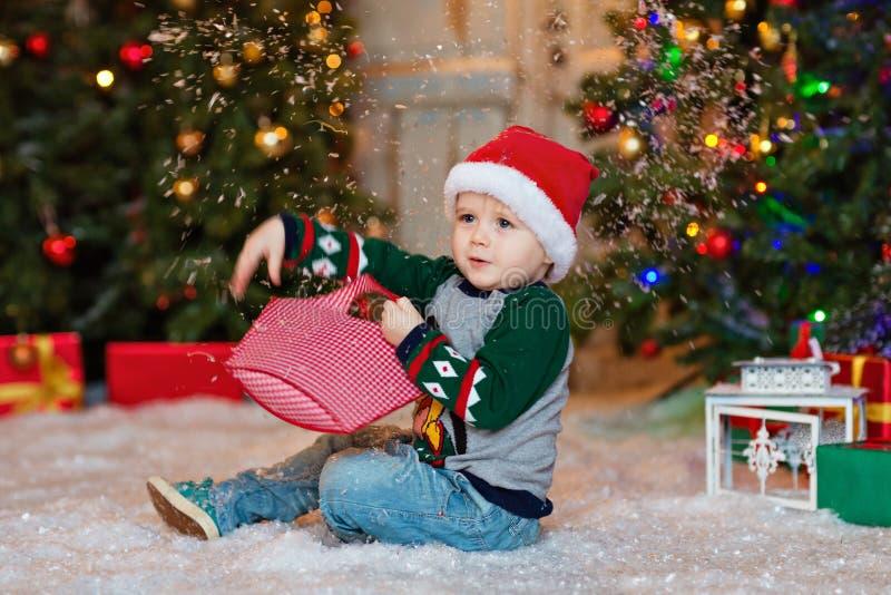El pequeño muchacho encantador rubio se sienta en nieve y lanza nieve en los vagos foto de archivo