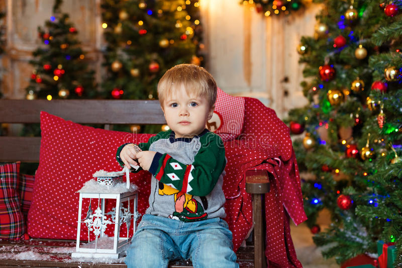 El pequeño muchacho encantador rubio se sienta en un banco y sostener una linterna imagen de archivo libre de regalías