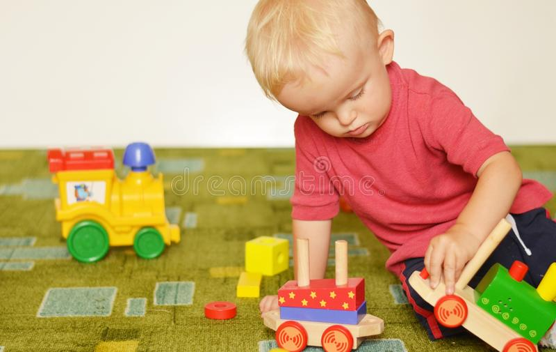 El pequeño muchacho está jugando con los trenes fotografía de archivo