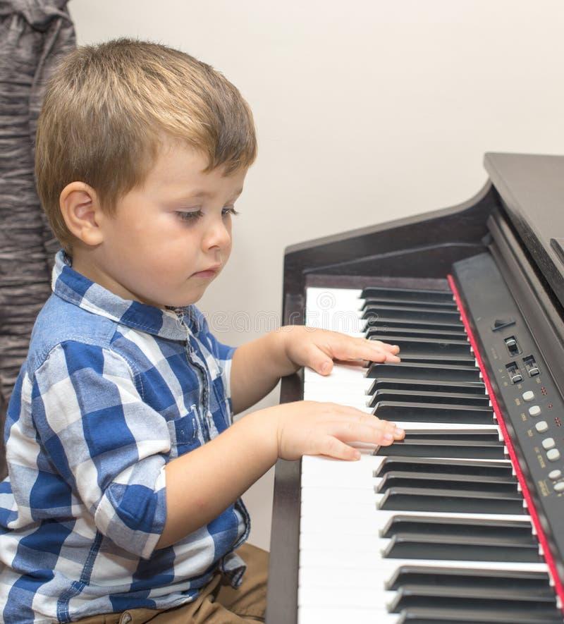 El pequeño muchacho feliz juega el piano imágenes de archivo libres de regalías