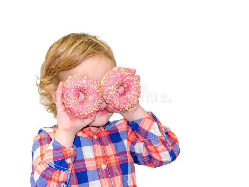 El pequeño muchacho lindo feliz está comiendo el buñuelo en la pared blanca del fondo foto de archivo libre de regalías