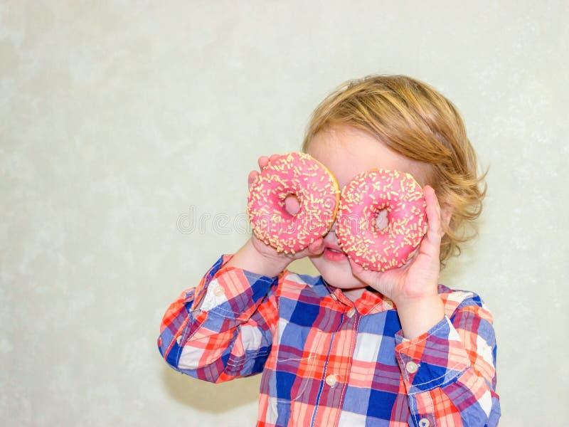 El pequeño muchacho lindo feliz está comiendo el buñuelo en la pared blanca del fondo imagen de archivo