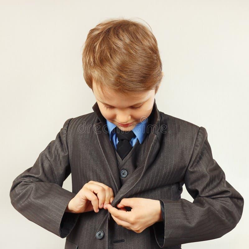 El pequeño muchacho lindo sujetó el traje de negocios imagen de archivo