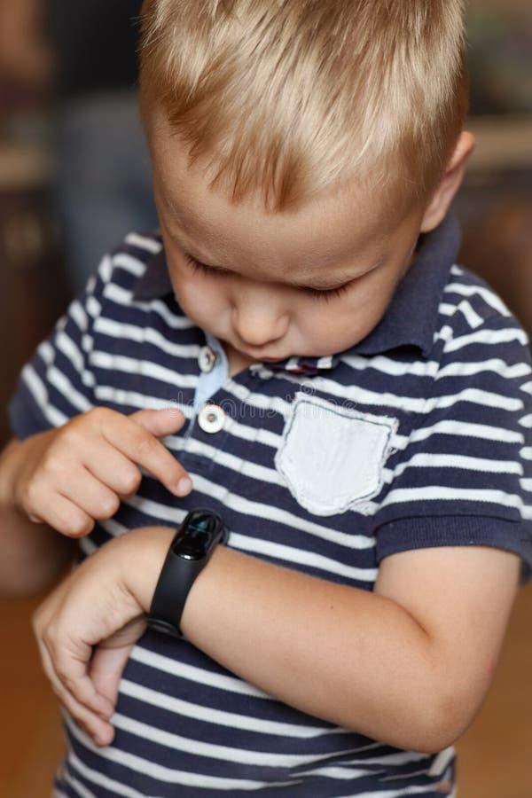 El pequeño muchacho rubio lindo con los ojos azules señala al perseguidor digital de la aptitud en su muñeca fotografía de archivo libre de regalías