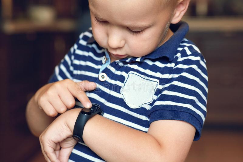 El pequeño muchacho rubio lindo con los ojos azules señala al perseguidor digital en su expresión seria de la muñeca, emociones f imagenes de archivo
