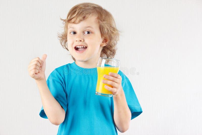 El pequeño muchacho rubio va a beber un zumo de naranja fresco imagen de archivo