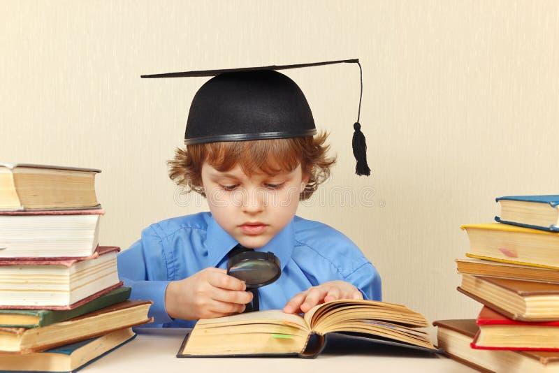 El pequeño muchacho serio en sombrero académico estudia los libros viejos con la lupa imagenes de archivo