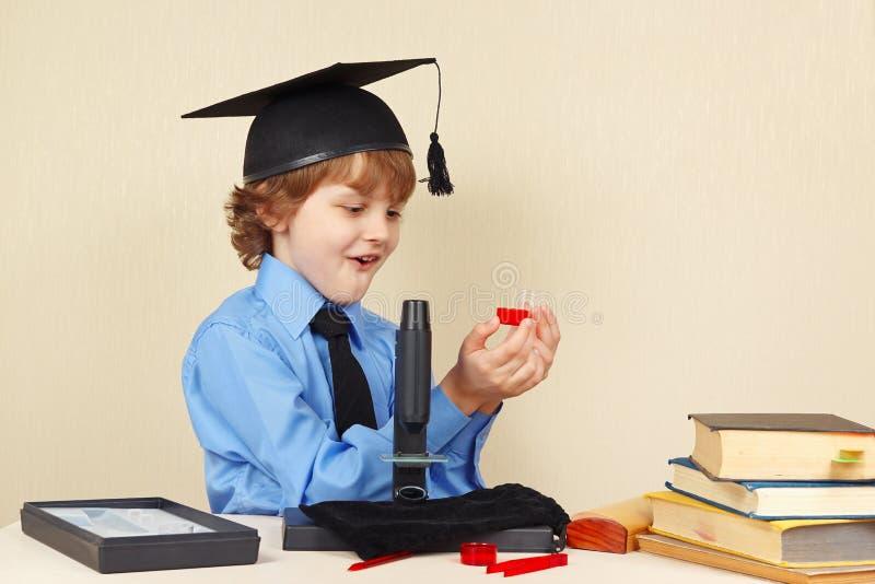 El pequeño muchacho sonriente en sombrero académico ve los resultados de la investigación al lado del microscopio imágenes de archivo libres de regalías