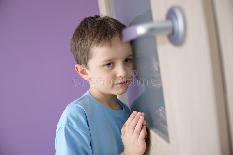 El pequeño muchacho triste oye por casualidad la lucha de sus padres fotografía de archivo