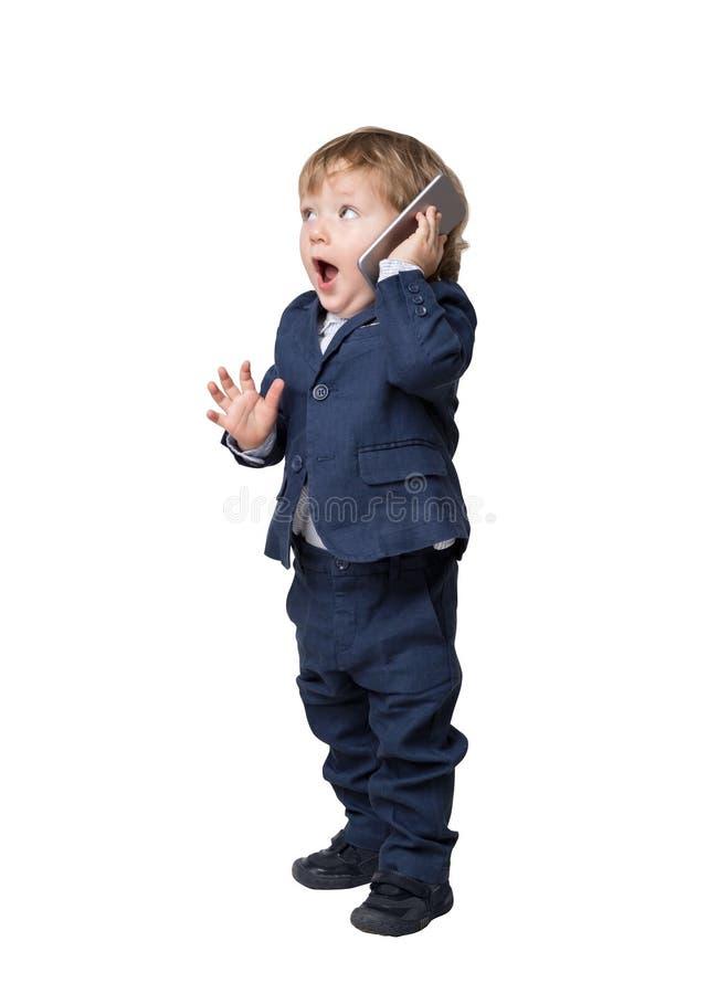 El pequeño niño adorable está hablando en el teléfono y está llevando un traje foto de archivo libre de regalías