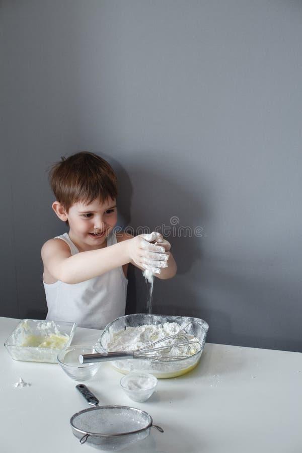 El pequeño niño alegre hace la torta dulce Añade la harina a la pasta El sentarse en una tabla blanca en un fondo gris Preparaci? imagen de archivo libre de regalías