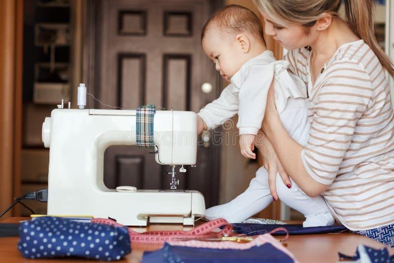 El pequeño niño aprende nuevo conocimiento, junto con su madre examina la máquina de coser Trabajo en casa, el parenting, padres  fotografía de archivo libre de regalías