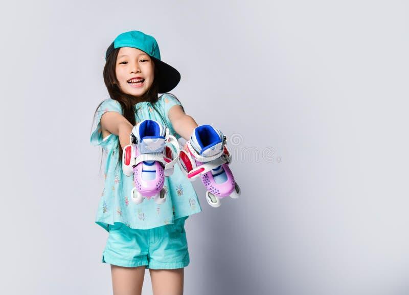 El pequeño niño asiático sonriente feliz del bebé en demostraciones azules claras del casquillo de la camiseta y del sombrero dem imagen de archivo