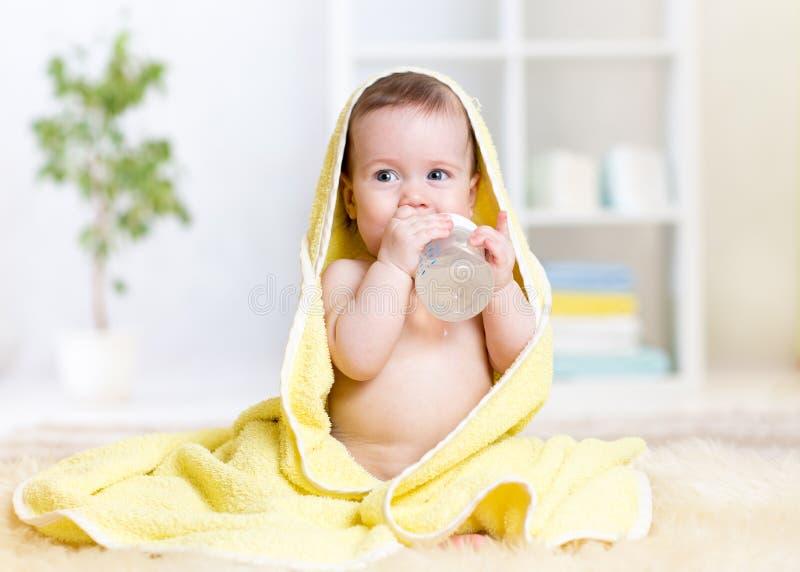 El pequeño niño bebe el agua de la botella envuelta adentro imágenes de archivo libres de regalías