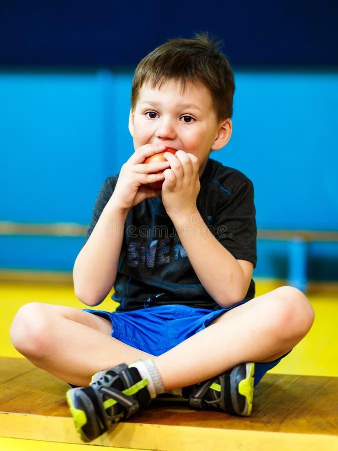 El pequeño niño come una manzana fotografía de archivo libre de regalías