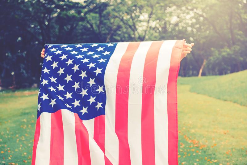 El pequeño niño del niño feliz que corre con la bandera americana los E.E.U.U. celebra fotos de archivo