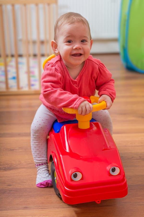 El pequeño niño es que juega y de conducción del coche del rojo del juguete imágenes de archivo libres de regalías