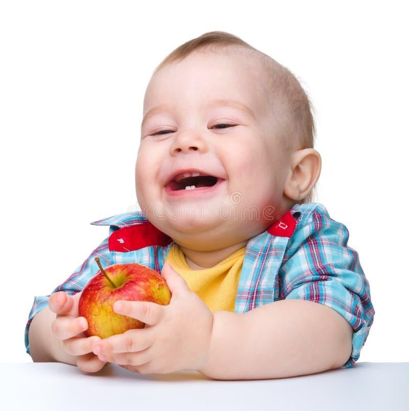 El pequeño niño está comiendo la manzana roja y la sonrisa foto de archivo