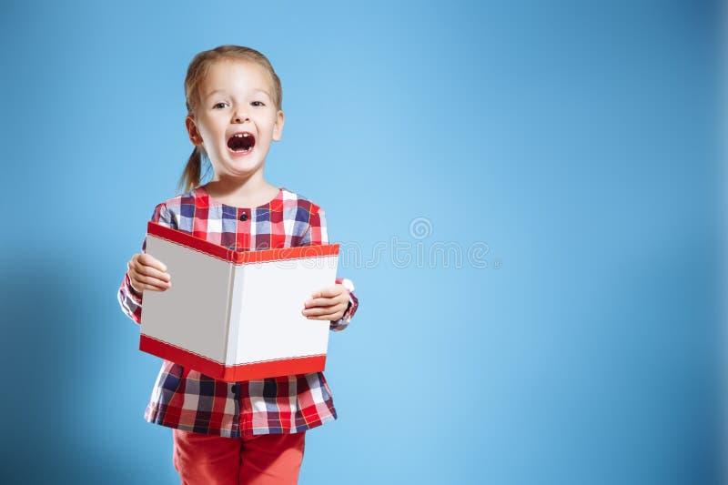 El pequeño niño está leyendo un libro Embrome en el fondo de la pared brillante del color Concepto de la educación imagen de archivo libre de regalías