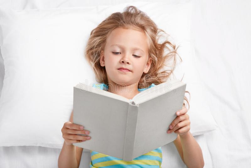 El pequeño niño femenino atractivo descansa en cama con el libro, lee historia emocionante interesante antes de sueño, mira atent fotografía de archivo
