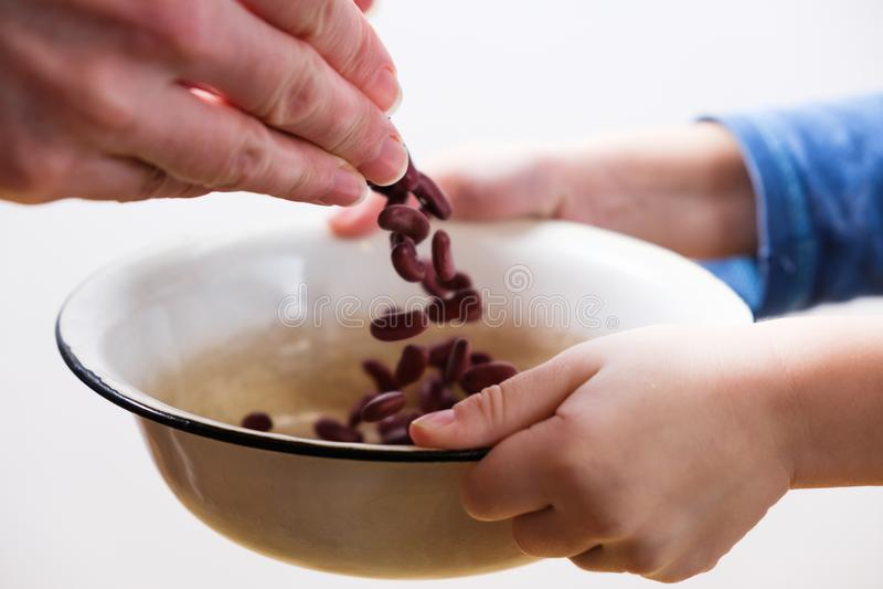 El pequeño niño hambriento consigue la comida dona ayuda un voluntario, con el cuenco lleno de habas imagen de archivo libre de regalías