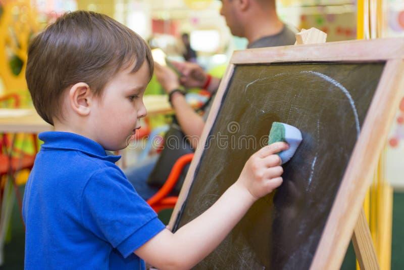 El pequeño niño limpia el tablero de tiza imagen de archivo libre de regalías