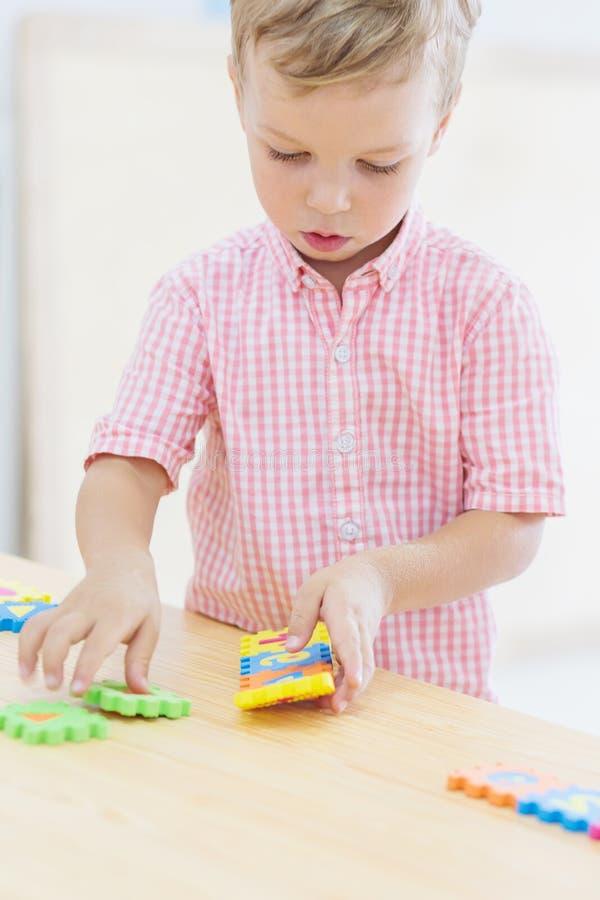 El pequeño niño lindo enfocado recoge rompecabezas fotos de archivo libres de regalías