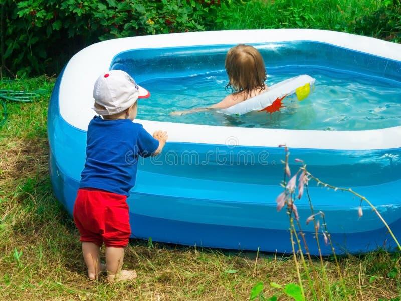 el pequeño niño pequeño mira con interés en el lado de la piscina para su natación de la hermana en el agua T imagenes de archivo
