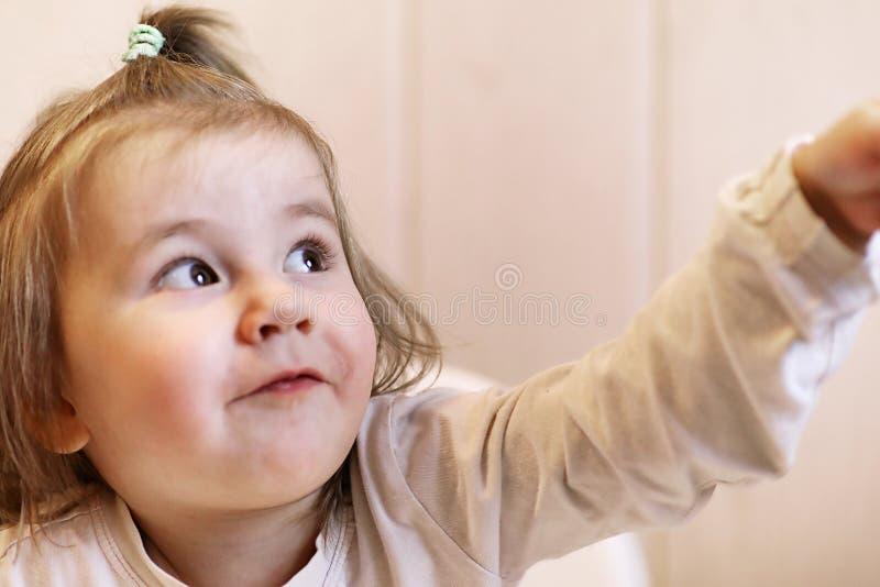 El pequeño niño que sonríe y tiene fondo del blanco de la diversión imagen de archivo