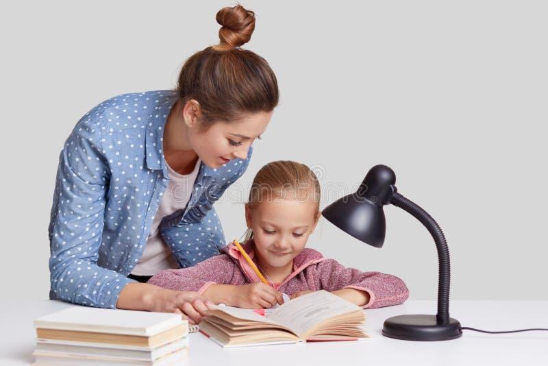 El pequeño niño reescribe la información en cuaderno, ha satisfecho la expresión, su madre se coloca cerca, los intentos a la hij imagen de archivo libre de regalías