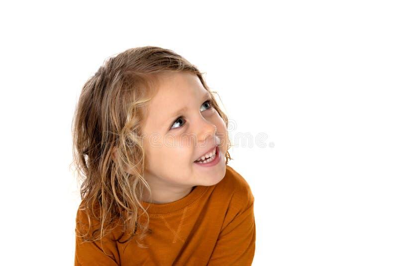 El pequeño niño rubio que se imaginaba algo aisló en un backgr blanco foto de archivo
