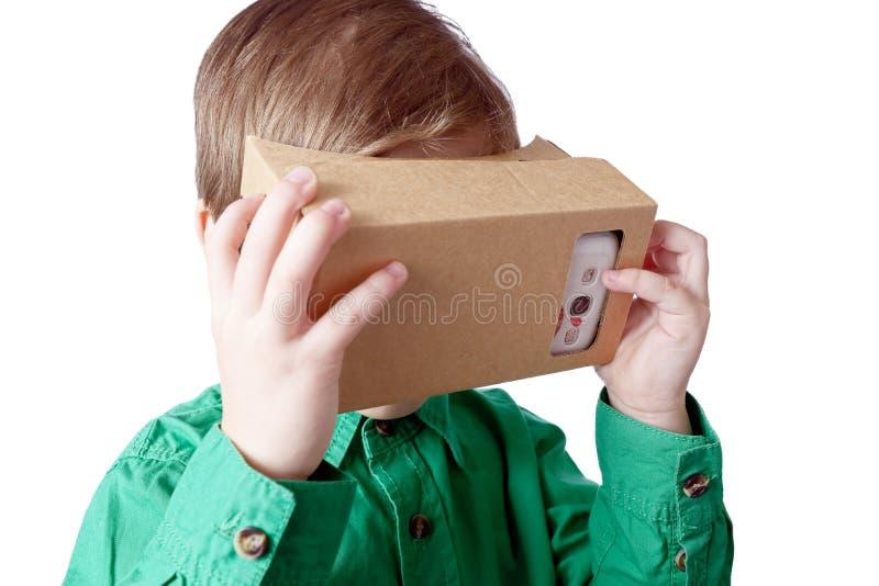 El pequeño niño utiliza la realidad virtual (cartulina de VR) en el fondo blanco fotografía de archivo