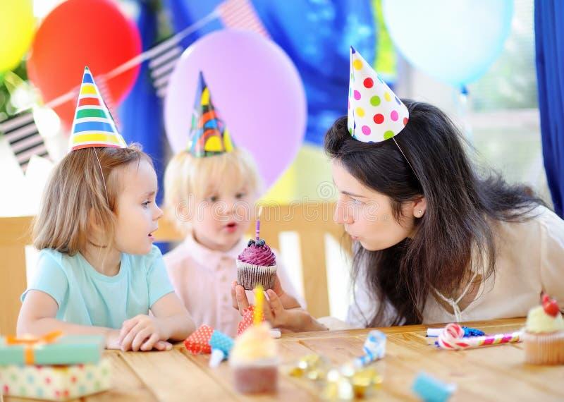 El pequeño niño y su madre celebran la fiesta de cumpleaños con la decoración colorida y las tortas con la decoración colorida y  foto de archivo libre de regalías