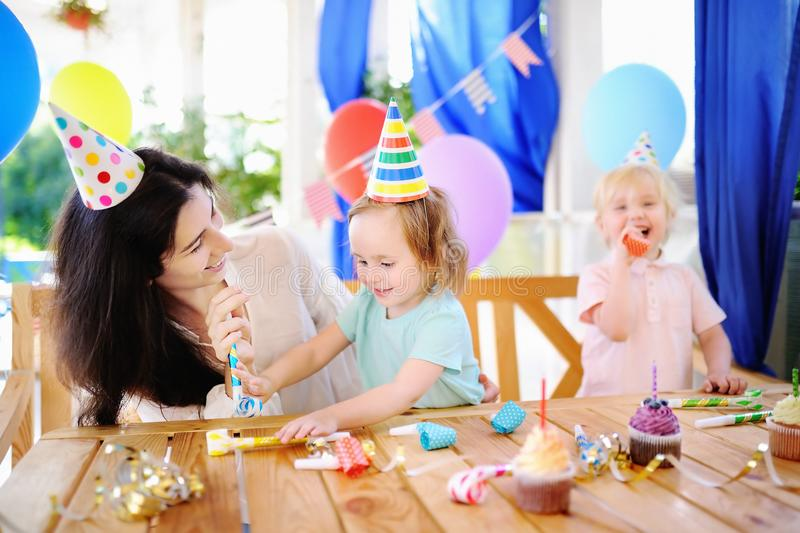 El pequeño niño y su madre celebran la fiesta de cumpleaños con la decoración colorida y las tortas con la decoración colorida y  fotos de archivo