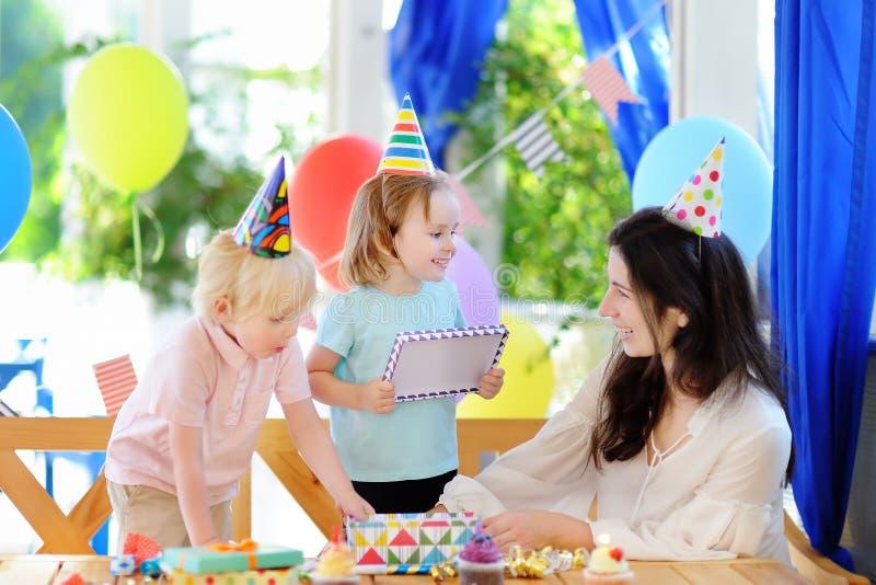 El pequeño niño y su madre celebran la fiesta de cumpleaños con la decoración colorida y las tortas con la decoración colorida y  foto de archivo