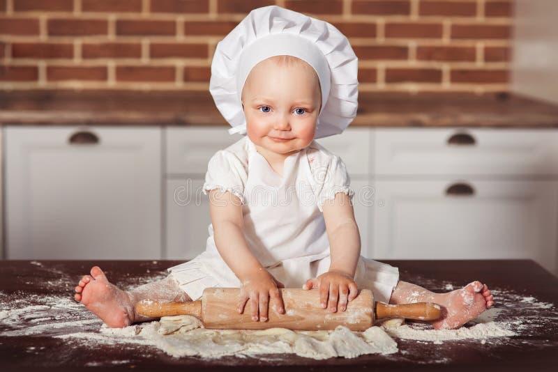 El pequeño panadero sonriente del bebé en el sombrero y el delantal blancos del cocinero amasa una pasta foto de archivo