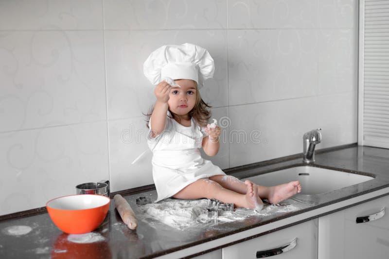 El pequeño panadero sonriente del bebé en el sombrero y el delantal blancos del cocinero amasa una pasta en cocina del tle imagen de archivo