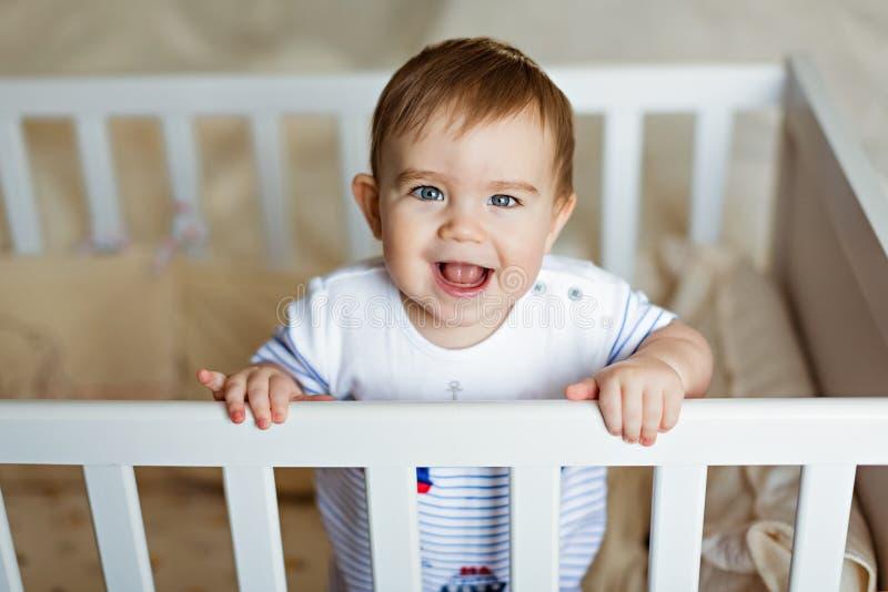 El pequeño pequeño muchacho rubio adorable lindo en un bodykit rayado está adentro fotos de archivo libres de regalías