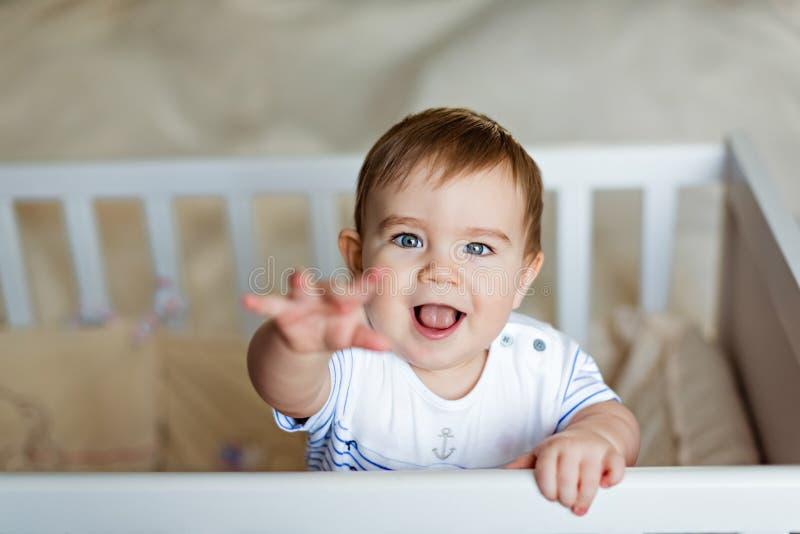 El pequeño pequeño muchacho rubio adorable lindo en un bodykit rayado está adentro fotografía de archivo
