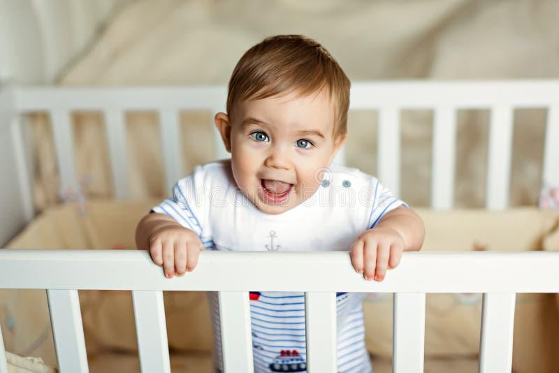 El pequeño pequeño muchacho rubio adorable lindo en un bodykit rayado está adentro fotos de archivo
