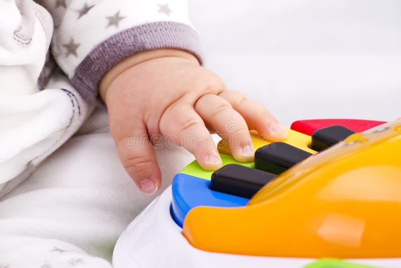 El pequeño pianista de la mano del bebé juega en un juguete colorido fotografía de archivo