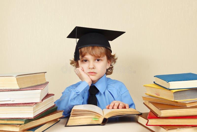 El pequeño profesor cansado en sombrero académico estudia los libros viejos imagenes de archivo