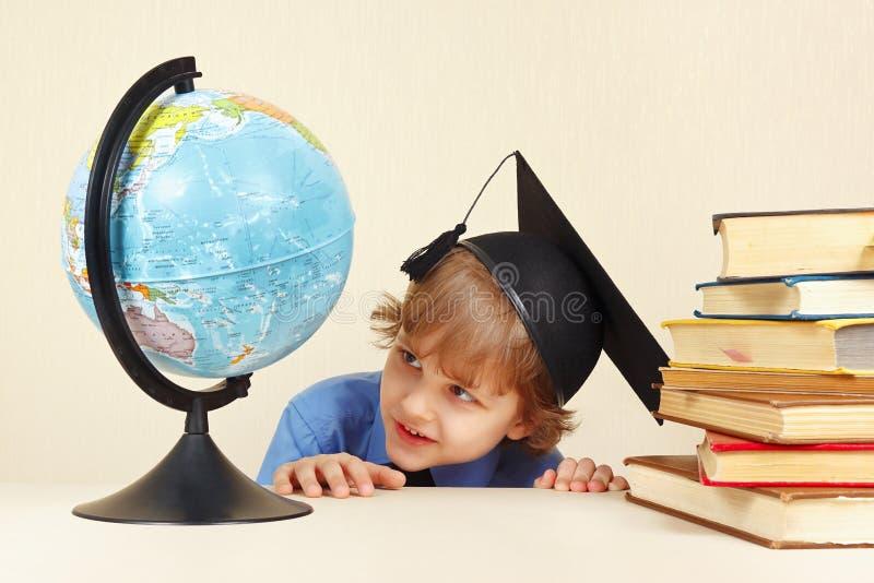 El pequeño profesor sonriente en sombrero académico mira el globo geográfico imagenes de archivo