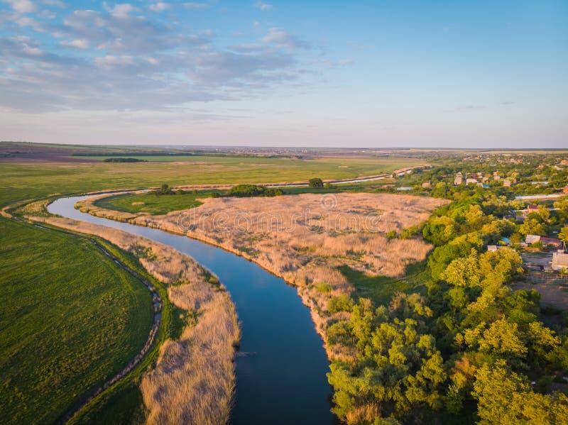 El pequeño pueblo y el río reservado serpentea en medio de campos y de prados verdes en la puesta del sol Paisaje hermoso con un  fotografía de archivo