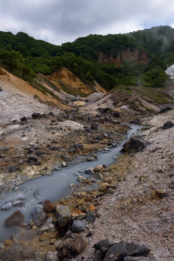 El pequeño río fluye a través de las rocas del valle Jigokudani del infierno imagenes de archivo